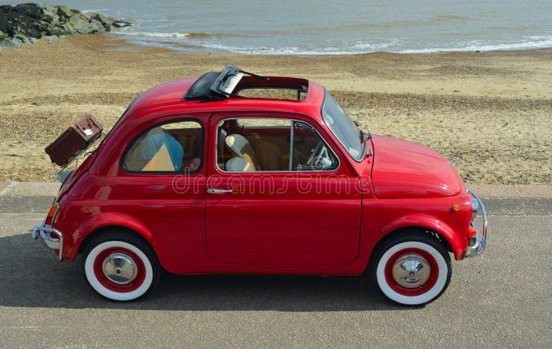 有野餐篮子的经典红色菲亚特500汽车在沿海岸区散步停放了 库存照片