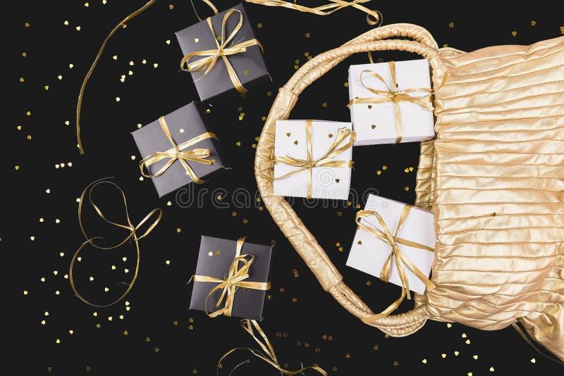 有金丝带的黑白礼物盒从金黄袋子出去 图库摄影