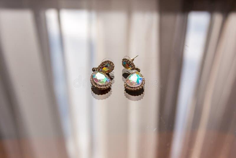 有金刚石宏指令的耳环在玻璃和亮光说谎在阳光下用不同的颜色 库存图片