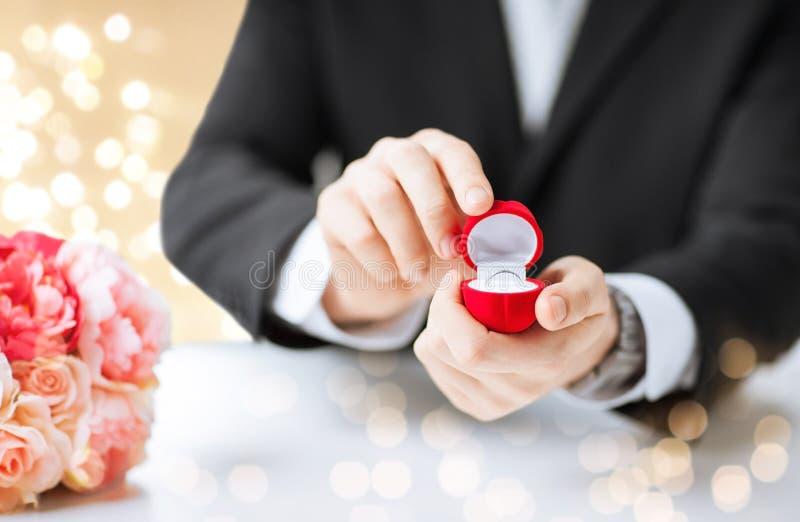 有金刚石定婚戒指的人在红色礼物盒 图库摄影