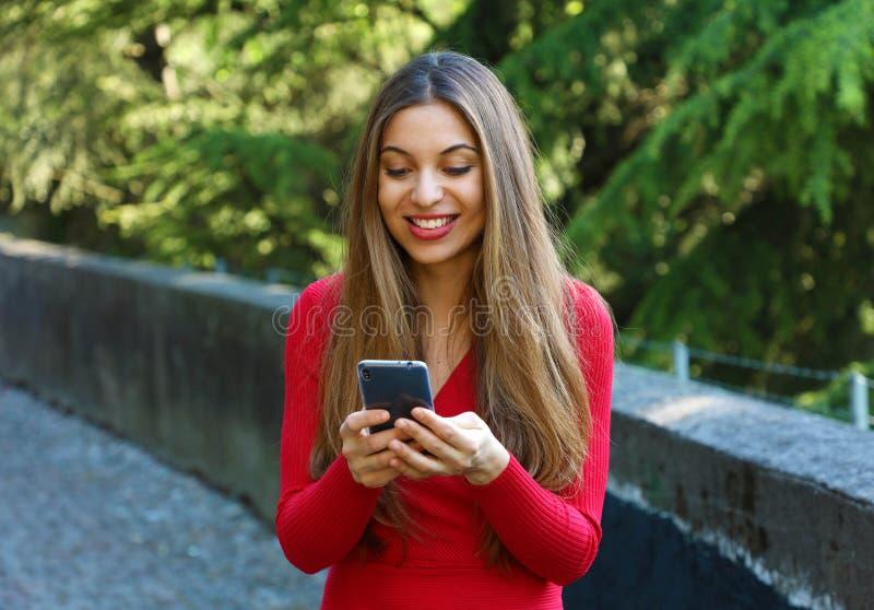 有金发传讯的美丽的年轻女人在智能手机在城市公园 有相当的女孩智能手机交谈 库存照片