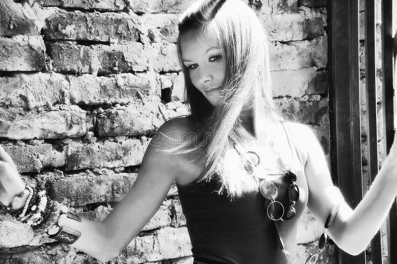 有金发光的年轻性感的相当美丽的女孩模型妇女点燃了砖墙 库存照片