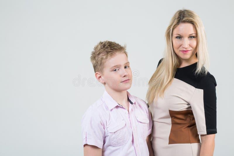 有金发和一个儿子的母亲有被弄乱的头发的 免版税库存图片