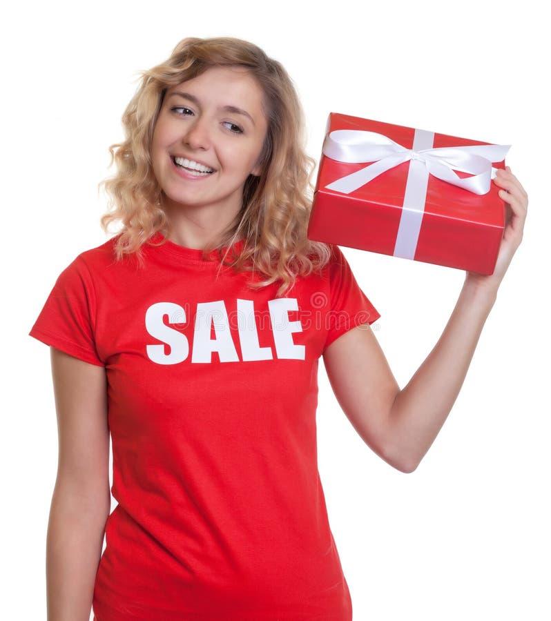 有金发和礼物的妇女在销售衬衣 库存图片