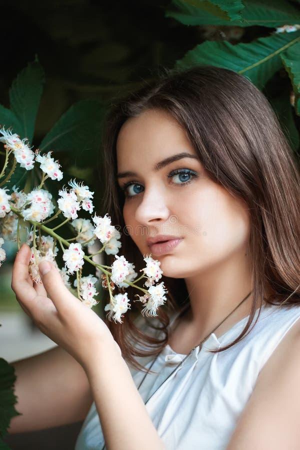 有金发和蓝眼睛的美女在她的手上的拿着栗子花 ?? 轻的构成和宽松长发 免版税库存照片