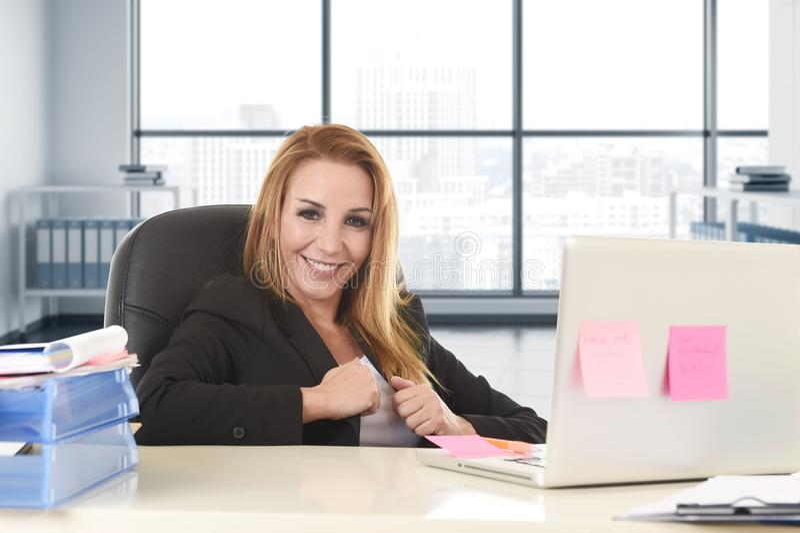 有金发微笑的确信倾斜的独裁的女商人在运作在便携式计算机的办公室椅子 免版税库存照片