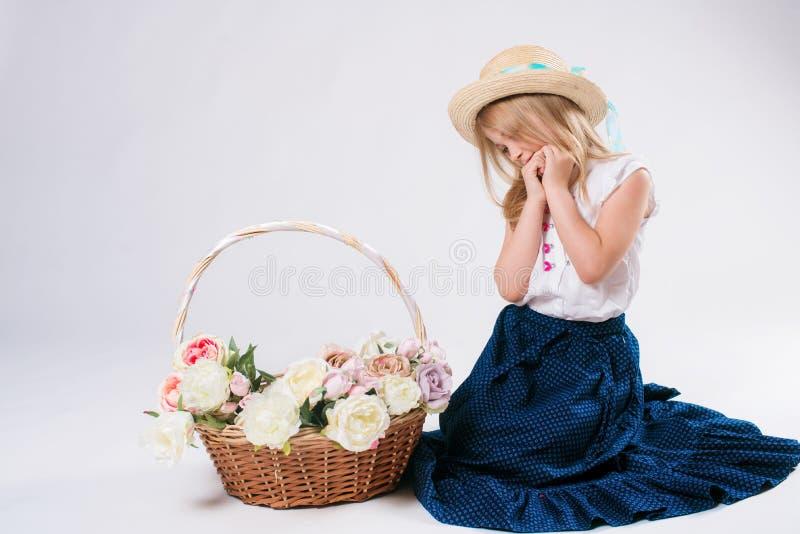 有金发有花篮子的和kanotier的草帽的美丽的时兴的小女孩 免版税库存图片