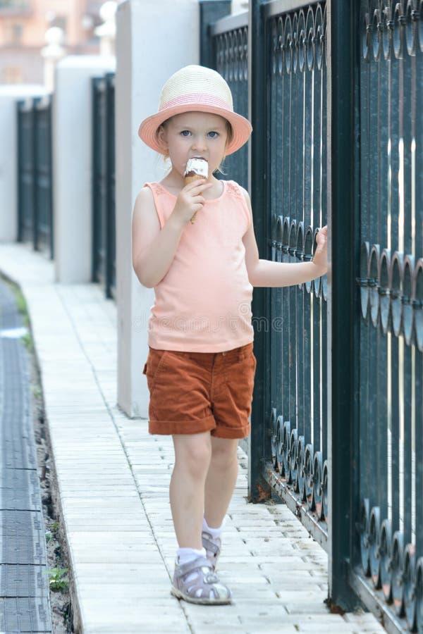 有金发的一个小女孩去并且吃冰淇凌 免版税库存图片
