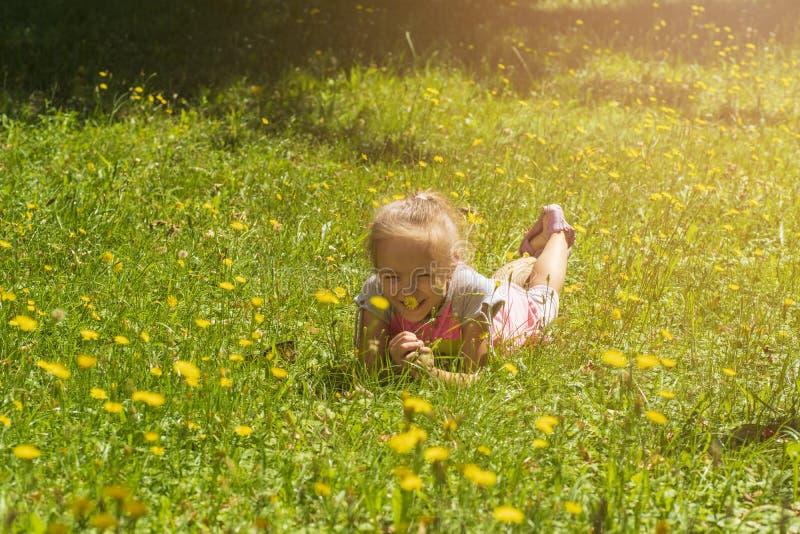 有金发的一个小女孩在绿草和嗅蒲公英说谎 免版税库存图片