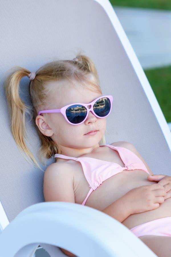 有金发的一女孩在太阳镜晒日光浴 孩子是在度假,说谎在太阳懒人 免版税图库摄影