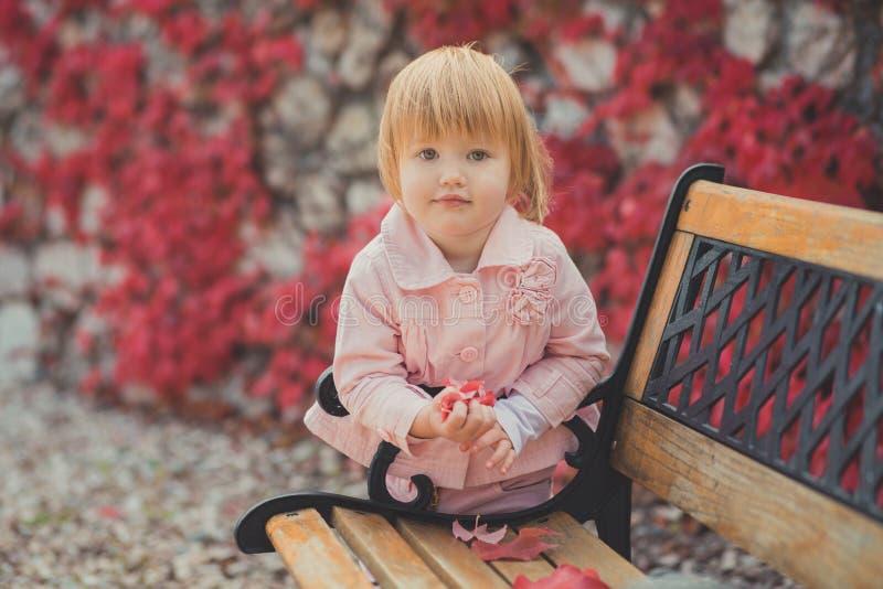 有金发的享受春天秋天的婴孩逗人喜爱的女孩和桃红色苹果面颊计时充分摆在美丽的庭院里的假日花 免版税图库摄影