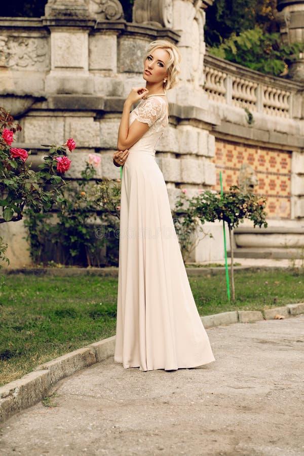 有金发的华美的新娘佩带豪华礼服和辅助部件 免版税库存图片