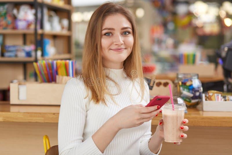 有金发的友好的女孩,休息在咖啡馆在早晨,花费与朋友、饮用的coctail和用途智能手机,检查的时间 库存照片