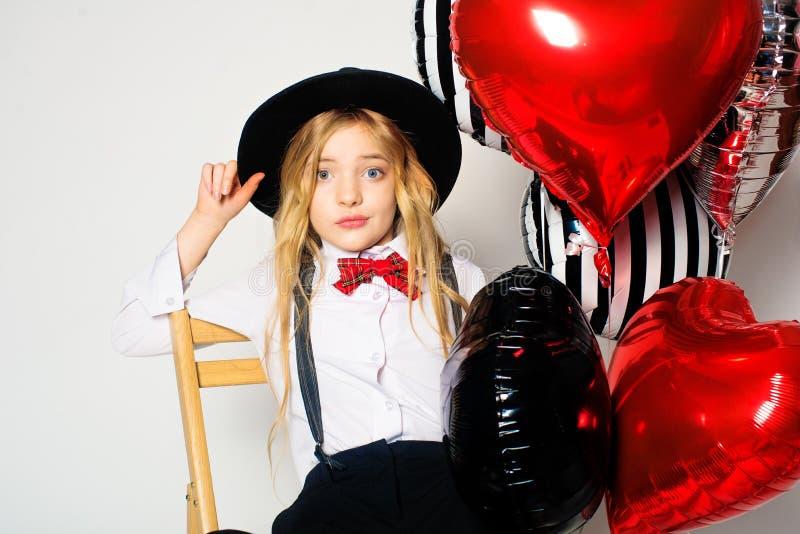 有金发的可爱的女孩在一件黑帽会议和一条红色bowtie领带明亮的气球心脏和礼物为情人节 免版税图库摄影