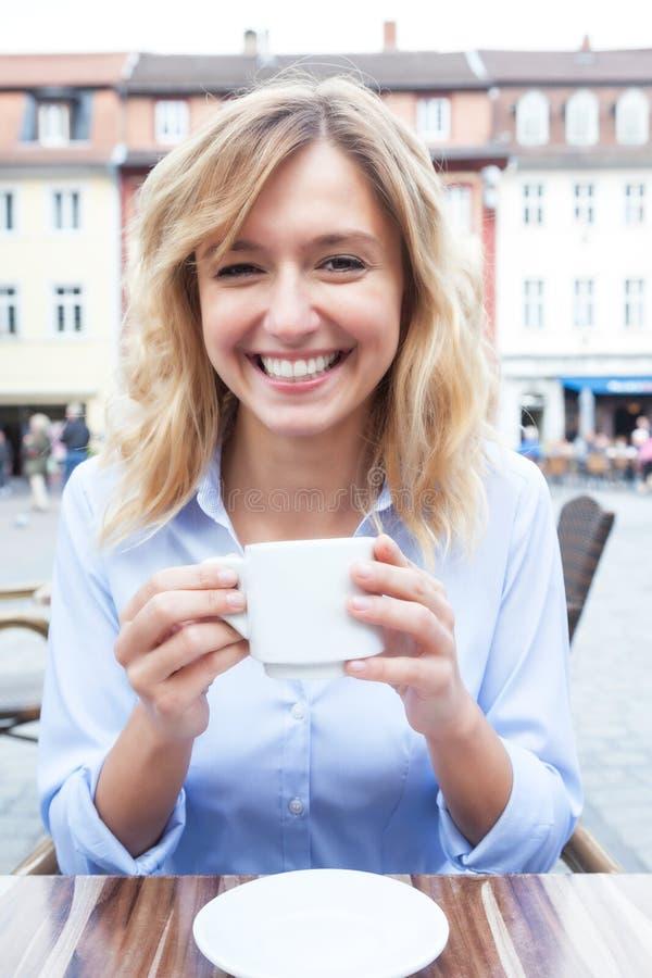 有金发的可爱的妇女喝咖啡的 库存图片