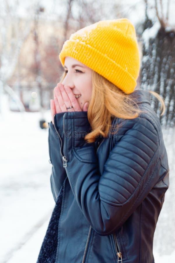 有金发的可爱的年轻女人在冬天公园温暖她的手 免版税库存图片