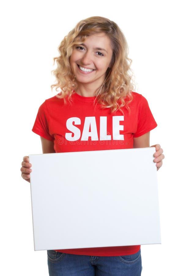 有金发的妇女在拿着牌的销售衬衣 免版税库存照片