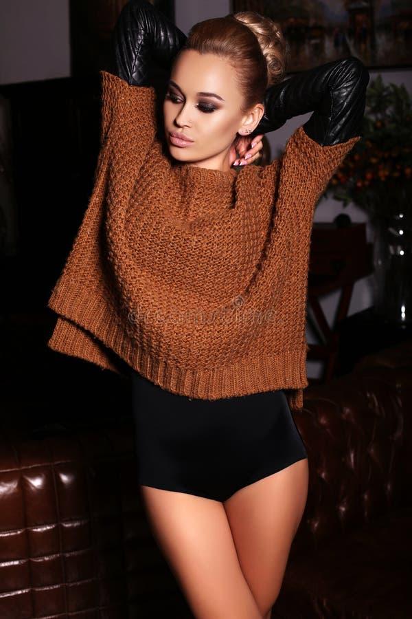 有金发的妇女戴着舒适羊毛衫和皮手套 图库摄影