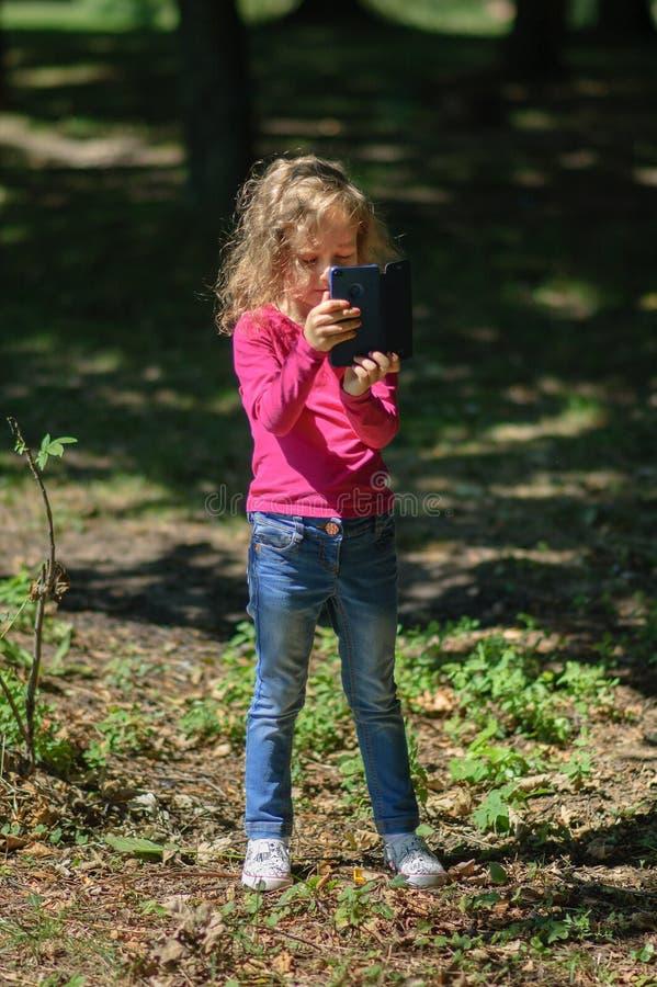 有金发的小逗人喜爱的女孩在公园使用站立蓝色的智能手机 拍照片的女孩由机动性 免版税图库摄影