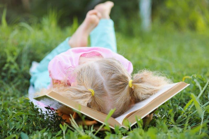 有金发的小逗人喜爱的女孩疲倦了读书和coveri 免版税库存图片