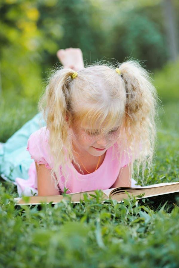 有金发的小逗人喜爱的女孩读一本书的在户外 免版税图库摄影