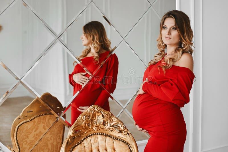 有金发的年轻美丽的孕妇和在摆在大镜子附近的时兴的红色礼服的柔和的构成在演播室 免版税库存图片