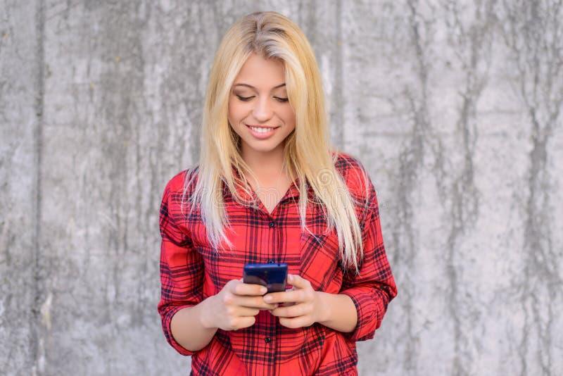 有金发的微笑的愉快的快乐的妇女,在使用流动3g, 4g的方格的衬衣interent为聊天和传送信息s 图库摄影