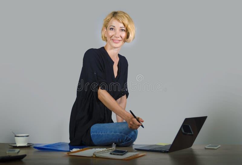 有金发的微笑,当工作放松在办公室l时的年轻美丽和愉快的妇女被隔绝的公司业务画象  库存照片