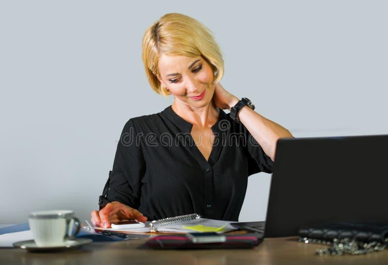 有金发的微笑,当工作放松对办公室膝上型计算机com时的年轻美丽和愉快的妇女公司业务画象  免版税库存照片