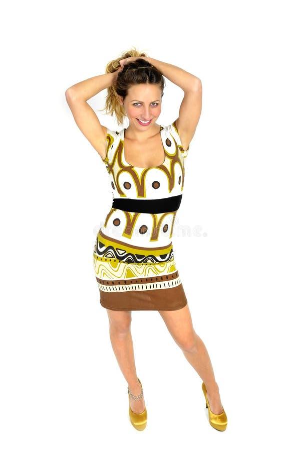 有金发的性感的可爱的妇女在短的时髦礼服和高跟鞋摆在诱人在女性时尚概念 图库摄影
