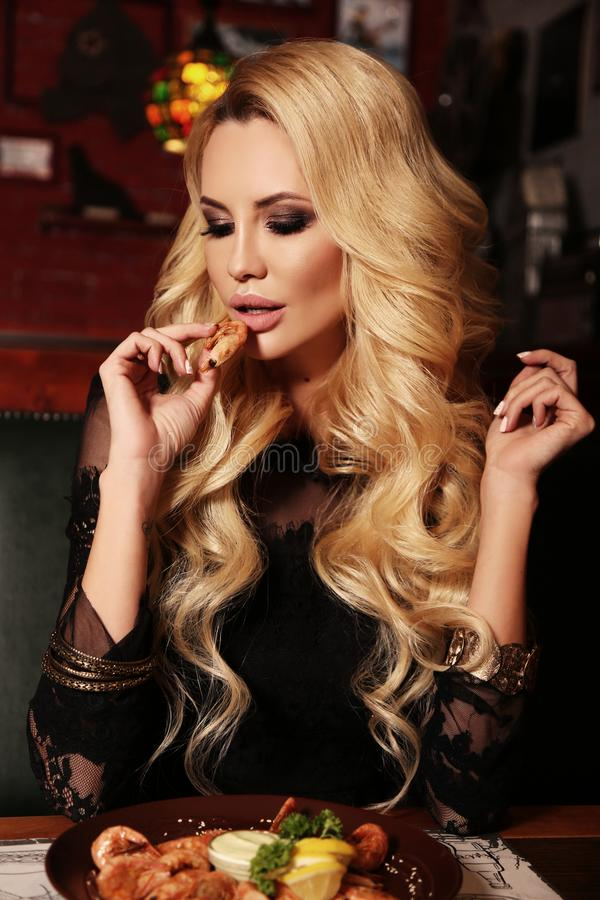 有金发的性感的妇女吃可口汉堡包的 免版税图库摄影