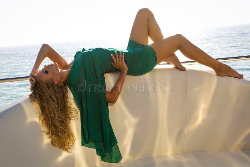 有金发的性感的妇女在摆在游艇的典雅的绿色礼服 库存照片