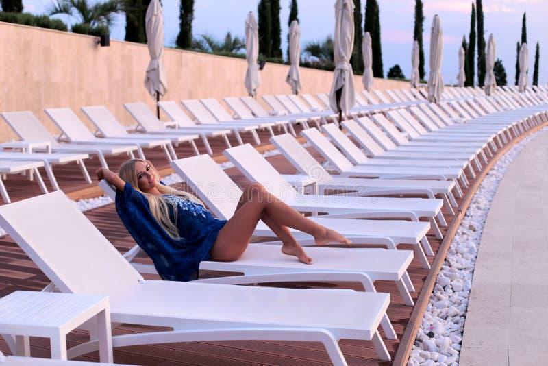 有金发的性感的妇女在摆在luxurio附近的典雅的比基尼泳装 图库摄影