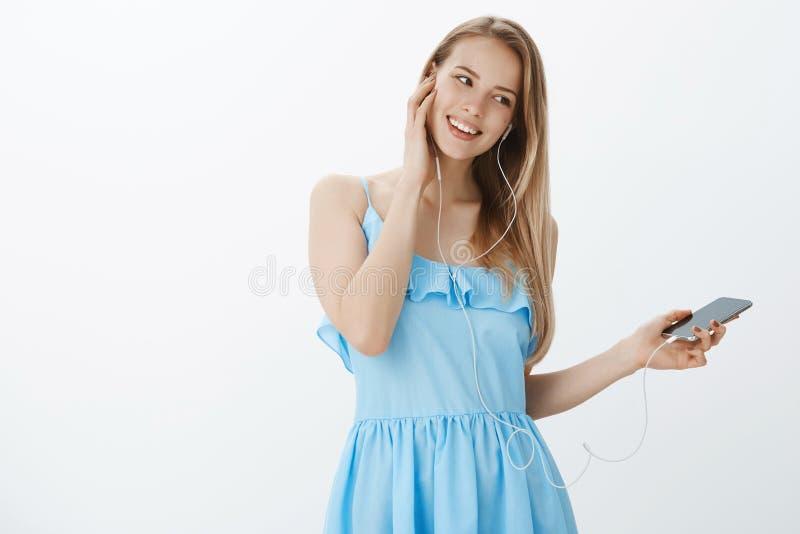 有金发的无忧无虑的吸引人和愉快的年轻时髦的欧洲妇女在掀动头和接触的蓝色礼服 库存照片