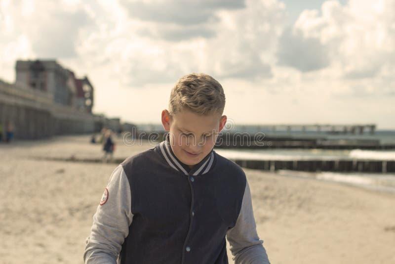 有金发的男孩走在beach3的 库存图片