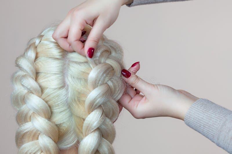 有金发的美丽的女孩,美发师编织一个辫子特写镜头,在美容院 免版税库存照片