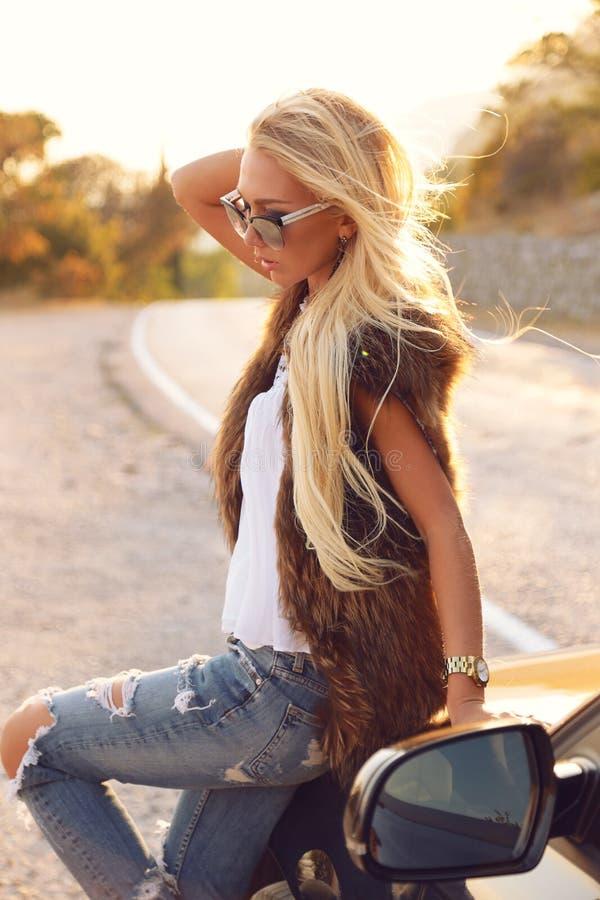 有金发的美丽的妇女在典雅的成套装备,摆在路 免版税库存图片