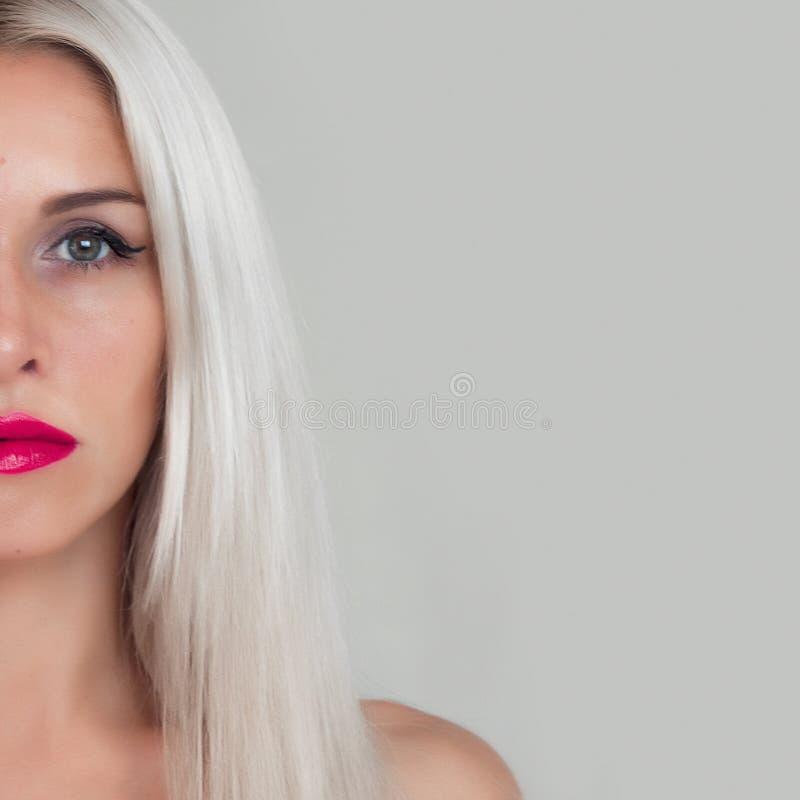 有金发的美丽的妇女 与红色唇膏和红色钉子的时装模特儿 免版税库存照片