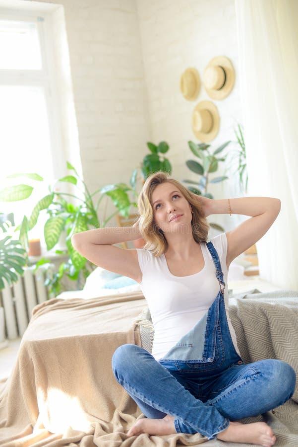 有金发的美丽的孕妇在一白色T恤和蓝色牛仔裤在有许多的一间屋子里居住绿色植物 免版税图库摄影