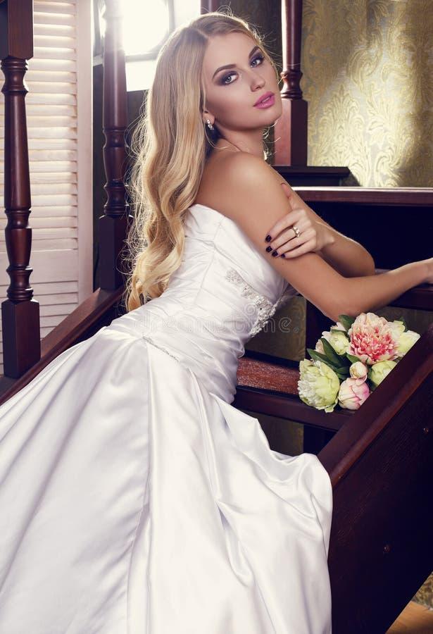 有金发的美丽的新娘在与花束的典雅的婚礼礼服 库存照片