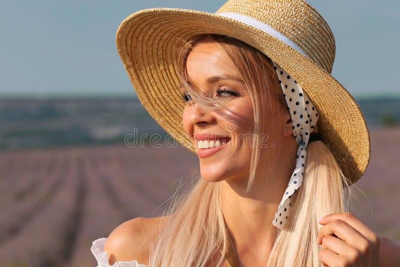有金发的美女在典雅的摆在开花的淡紫色领域的衣裳和辅助部件 库存图片