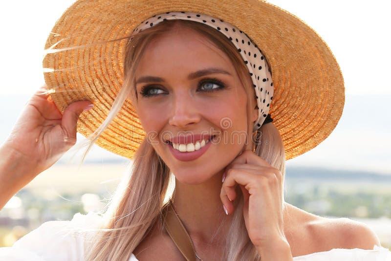 有金发的美女在典雅的摆在开花的淡紫色领域的衣裳和辅助部件 图库摄影