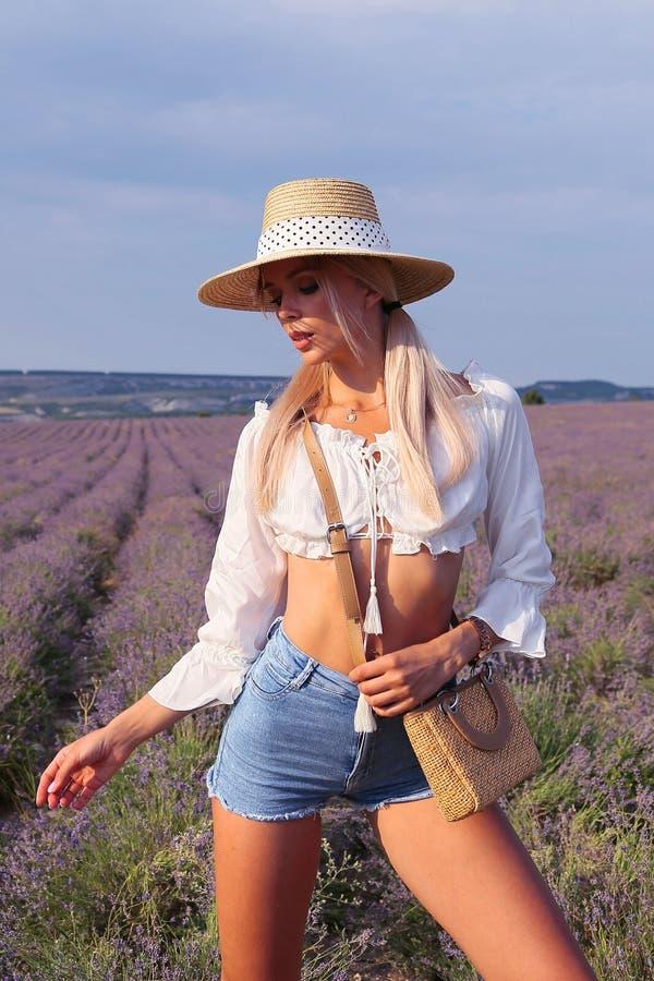有金发的美女在典雅的摆在开花的淡紫色领域的衣裳和辅助部件 免版税库存图片