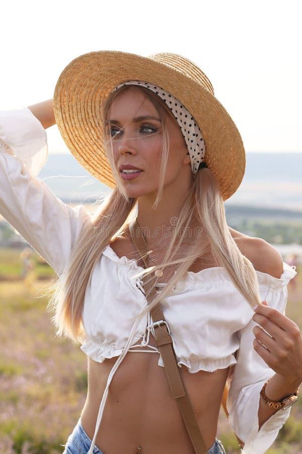 有金发的美女在典雅的摆在开花的淡紫色领域的衣裳和辅助部件 免版税库存照片