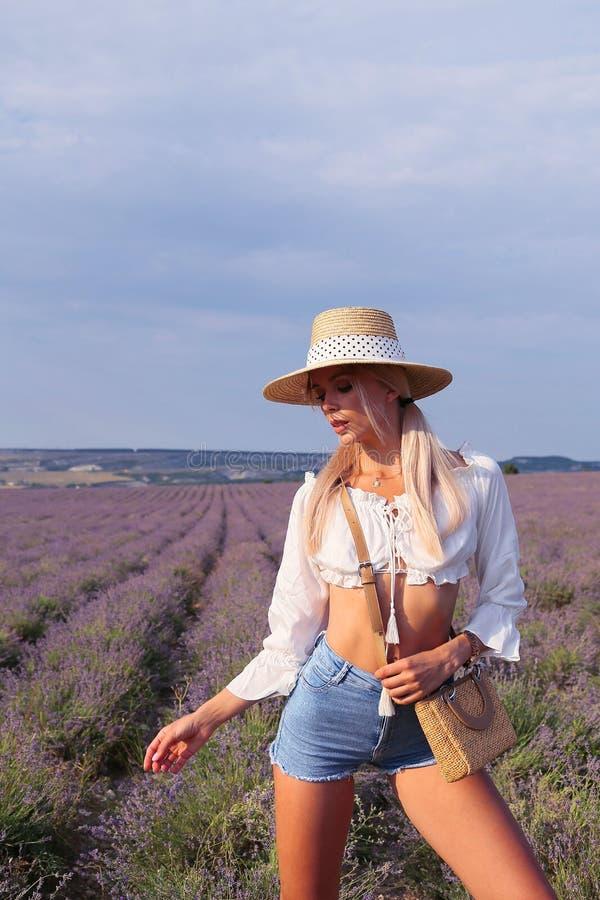 有金发的美女在典雅的摆在开花的淡紫色领域的衣裳和辅助部件 免版税图库摄影