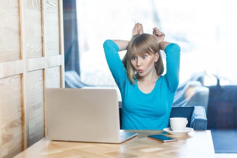 有金发的自由职业者在蓝色T恤杉在咖啡馆在膝上型计算机坐并且打视频通话,谈话和戏弄与她 库存图片
