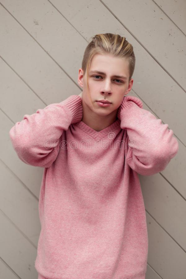有金发的英俊的年轻人在时尚桃红色毛线衣 免版税库存图片