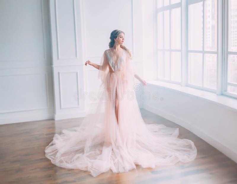 有金发的逗人喜爱的可爱的公主在摆在大窗口阳光,睡美人下的桃红色轻的礼服醒了 免版税库存照片