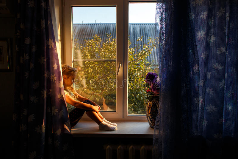 有金发的逗人喜爱的女孩坐窗台,注视着窗口日落 免版税库存照片