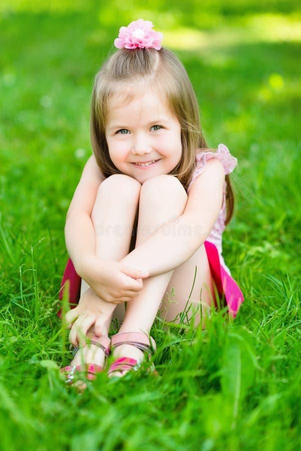 有金发的逗人喜爱的小女孩坐草 免版税图库摄影